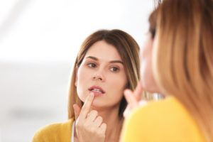 a woman looks in the mirror and points at a cold sore on her lip