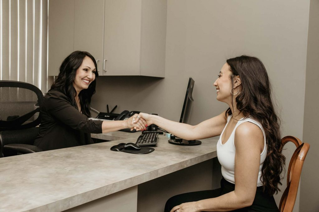 a receptionist and a dental patient sitting across from one another and shaking hands
