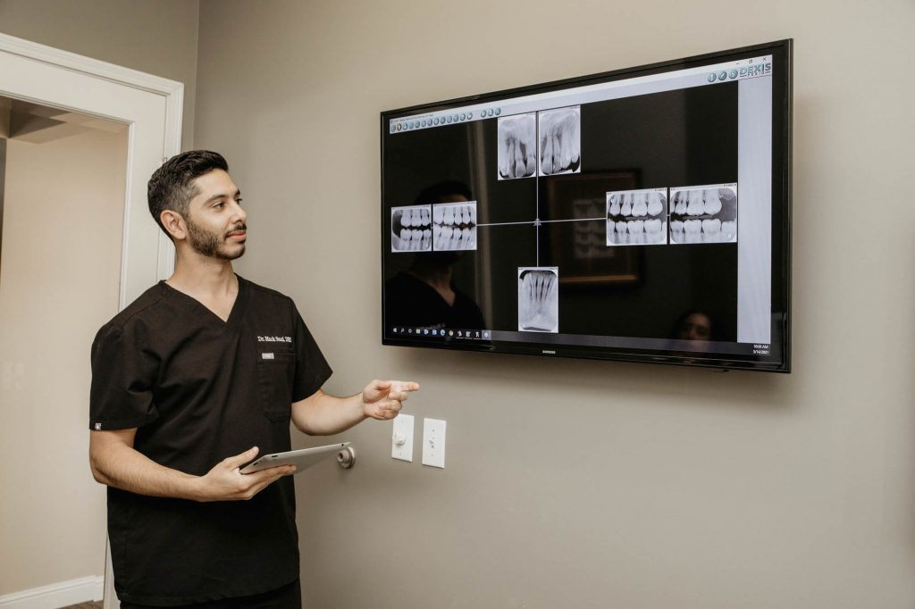 a dentist pointing at a tv screen displaying x-rays of teeth